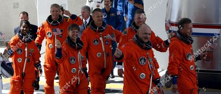 The Sts-121 Nasa Flight Crew Leaving the Operations and Checkout Building (onc) Under Tight Security at Kennedy Space Center (ksc) Cape Canaveral Florida Tuesday 04 July 2006 For Launch Pad 39b Astronauts (l-r) Stephanie D Wilson European Space Agency (esa) Astronaut Thomas Reiter of Germany Mission Specialist Lisa M Nowak Michael E Fossum Piers J Sellers Pilot Mark E Kelly and Commander Steven W Lindsey Wave Before Entering the Van That Will Transport the Crew to the Launch Pad