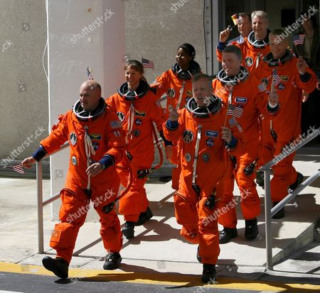 The Sts-121 Nasa Flight Crew Leaves the Operations and Checkout Building (onc) Under Tight Security at Kennedy Space Center (ksc) Cape Canaveral Florida Tuesday 04 July 2006 For Launch Pad 39b Astronauts (l-r) Pilot Mark E Kelly Commander Steven W Lindsey Mission Specialist Lisa M Nowak Michael E Fossum Piers J Sellers Stephanie D Wilson and European Space Agency (esa) Astronaut Thomas Reiter of Germany Wave Before Entering the Van That Will Transport the Crew to the Launch Pad