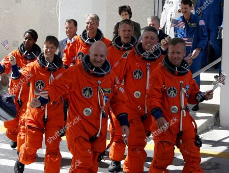 Stock Photo of The Sts-121 Nasa Flight Crew Leaving the Operations and Checkout Building (onc) Under Tight Security at Kennedy Space Center (ksc) Cape Canaveral Florida Tuesday 04 July 2006 For Launch Pad 39b Astronauts (left Row L-r) Stephanie D Wilson Mission Specialist Lisa M Nowak and Pilot Mark E Kelly (right Row L-r) European Space Agency (esa) Astronaut Thomas Reiter of Germany Michael E Fossum Piers J Sellers and Commander Steven W Lindsey Wave Before Entering the Van That Will Transport the Crew to the Launch Pad