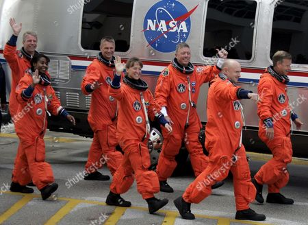 The Sts-121 Nasa Flight Crew Leaving the Operations and Checkout Building (onc) Under Tight Security at Kennedy Space Center (ksc) Cape Canaveral Florida Sunday 02 July 2006 For Launch Pad 39b Astronauts (l-r) Pilot Mark E Kelly Commander Steven W Lindsey Mission Specialist Lisa M Nowak Michael E Fossum Piers J Sellers Stephanie D Wilson and European Space Agency (esa) Astronaut Thomas Reiter of Germany Wave Before Entering the Van That Will Transport the Crew to the Launch Pad