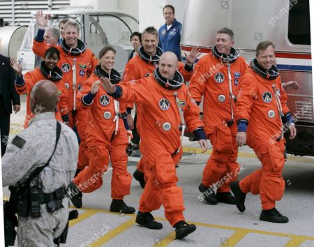The Sts-121 Nasa Flight Crew Leaving the Operations and Checkout Building (onc) Under Tight Security at Kennedy Space Center (ksc) Cape Canaveral Florida Thursday 15 June 2006 For Launch Pad 39b As Part of the Terminal Countdown Demonstration Tests (tcdt) the Tcdt is a Launch Dress Rehearsal That Occurs Prior to Each Shuttle Mission Astronauts (l-r)pilot Mark E Kelly Commander Steven W Lindsey Mission Specialist Lisa M Nowak Michael E Fossum Piers J Sellers Stephanie D Wilson and European Space Agency (esa) Astronaut Thomas Reiter of Germany Wave Before Entering the Van That Will Transport the Crew to the Launch Pad