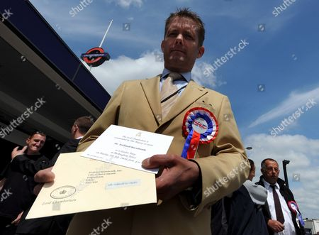 Stock Picture of Richard Barnbrook Bnp (british National Party) Councillor For Goresbrook Ward East London and Campaigning For the Bnp Holds His 07 July 2009 Garden Party Invitation From the Queen Elizabeth Ii in London Britain 04 June 2009 Polls For European Elections Opened Across Britain 04 June 2009