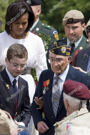 Us First Lady Michelle Obama (l) Louis Sarkozy and Son of French President Nicolas Sarkozy (bottom L) Escort an Unidentified Wwii Veteran (c) at a Memorial Ceremony to Mark the 65th Anniversary of the Allied Normandy Beach Landings in the Us War Cemetery in Colleville-sur-mer Normandy in Northern France 06 June 2009