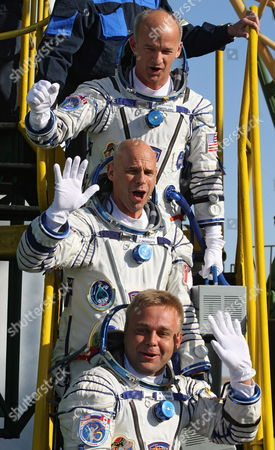Russian Cosmonaut Maxim Surayev (bottom) Canadian Billionaire and Space Tourist Guy Laliberte (c) and Nasa Astronaut Jeffrey Williams (top) Wave During a Farewell Ceremony As They Get Up Into the Spacecraft Soyuz Tma-16 Before the Launch at Baikonur Cosmodrome in Kazakhstan 30 September 2009 Russian Cosmonaut Maxim Surayev and Nasa Astronaut Jeffrey Williams to Arrive 02 October at the International Space Station Orbiting the Earth where They Will Live For the Next Six Months a Civilian Passenger Canadian Billionaire and Space Tourist Guy Laliberte Spent About $35 Million to Reserve His Spot On the Soyuz He Will Spend 12 Days Aboard the Orbiting Outpost and is Expected to Be the Last Space Tourist to Board the Station For at Least a Few Years Due to the Upcoming Retirement of Nasas Shuttle Fleet