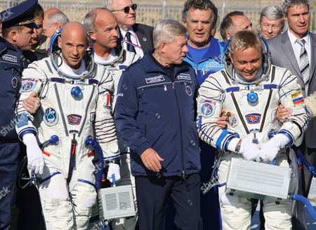 Russian Space Officials Help to Board Spacecraft Soyuz Tma-16 of Russian Cosmonaut Maxim Surayev (r) Nasa Astronaut Jeffrey Williams (c) and Canadian Billionaire and Space Tourist Guy Laliberte (l)before the Launch at Baikonur Cosmodrome in Kazakhstan 30 September 2009 Russian Cosmonaut Maxim Surayev and Nasa Astronaut Jeffrey Williams to Arrive 02 October at the International Space Station Orbiting the Earth where They Will Live For the Next Six Months a Civilian Passenger Canadian Billionaire and Space Tourist Guy Laliberte Spent About $35 Million to Reserve His Spot On the Soyuz He Will Spend 12 Days Aboard the Orbiting Outpost and is Expected to Be the Last Space Tourist to Board the Station For at Least a Few Years Due to the Upcoming Retirement of Nasas Shuttle Fleet