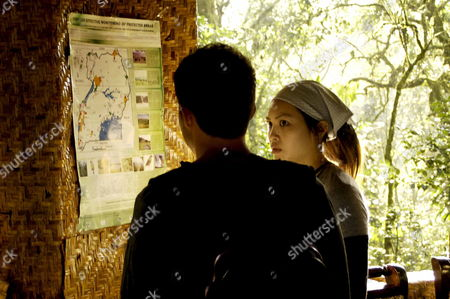 Stock Photo of Kristy Wu and Simon Curtis in Front of a Map Showing the Habitat of Different Animals in the Protected Areas of Uganda at Bwindi Impenetrable National Park Near Kisoro Uganda On 23 September 2009 Hollywood Celebrities Visited a Newly Discovered Family of Mountain Gorillas in the Impenetrable Forest Near Kisoro Which Will Be Part of the 'Friend a Gorilla' Facebook Campaign