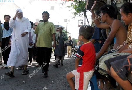 Muslim Cleric Abu Bakar Ba'asyir (l) Waves to Residents As He Walks to a Mosque Shortly Before a Prayer at His Boarding School in Solo Central Java Indonesia On Thursday 15 June 2006 Authorities Released Cleric Abu Bakar Bashir From Prison On Wednesday After He Served 26 Months in Prison For Giving His Blessing to the 2002 Bali Nightclub Bombings Freed Firebrand Indonesian Muslim Cleric Abu Bakar Baasyir Called the Militants Who Carried out Terrorist Attacks As 'Misguided' Holy Warriors Saying He Did not Agree Wih Their Methods Local Media Reports Said Thursday