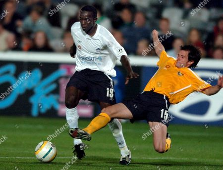 Central Coast Mariners Player Andrew Clark Tries to Tackle Sydney Fc Dwight Yorke (l) During the Pre Season Cup Match Against Central Coast Mariners at the Central Coast Stadium Tonight Saturday 30 July 2005