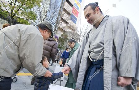 An Elderly Japanese Man Holds His Grand Son's Arm As He Shakes Hands with Bulgarian Sumo Wrestler Kotooshu As He and Other Wrestlers Gather Donations For Japanese Earthquake and Tsunami Victims in Front of a Train Station in Downtown Tokyo Japan 24 March 2011 the Number of People in Evacuation Centres in and Outside the Affected Areas is Approximately 261 000 Japan Tokyo