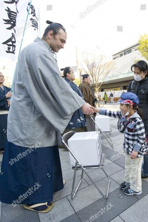 A Young Japanese Boy Shakes Hands with Bulgarian Sumo Wrestler Kotooshu As He and Other Wrestlers Gather Donations For Japanese Earthquake and Tsunami Victims in Front of a Train Station in Downtown Tokyo Japan 24 March 2011 the Number of People in Evacuation Centres in and Outside the Affected Areas is Approximately 261 000 Japan Tokyo