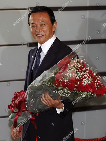 Holding a Bouquet Japan's Outgoing Prime Minister Taro Aso Smiles As He Leaves His Official Residence in Tokyo Japan 16 September 2009 His Successor Democratic Party of Japan Leader Yukio Hatoyama is Set to Be Elected As Japan's New Prime Minister Later in the Day and to Launch a New Coalition Government Japan Tokyo