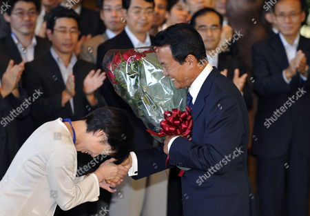 Japan's Outgoing Prime Minister Taro Aso (r) Receives a Bouquet From a Staff Member As He Leaves His Official Residence in Tokyo Japan 16 September 2009 His Successor Democratic Party of Japan Leader Yukio Hatoyama is Set to Be Elected As Japan's New Prime Minister Later in the Day and to Launch a New Coalition Government Japan Tokyo