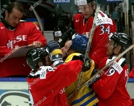 St Petersburg Russian Federation : Swiss Players Claudio Micheli (l) and Jean-jacque Aeschlimann Attack Swedish Peter Andersson (c) During Their Qualifying Match at the Ice Hockey World Championship in St Petersburg Saturday 06 May 2000 the Score After the Game is 1-1 (electronic Image)