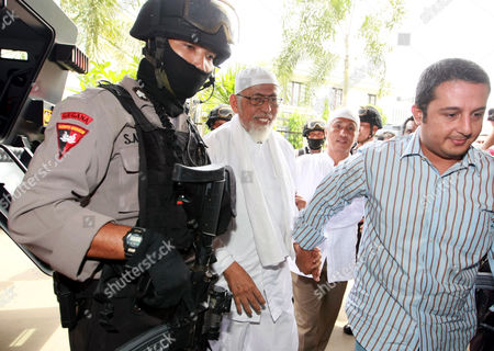 Stock Photo of Indonesian Muslim Cleric Abu Bakar Baasyir (c) is Escorted by Indonesian Police Officer As He Arrives at the Counsel For the Prosecution Office in Jakarta Indonesia 13 December 2010 the Indonesian Police Also Registered Cases of Terrorism Suspects Ba'asyir's File to the Attorney General Caregiver Al-mukmin Ngruki an Islamic Boarding School in Java Set Up by Baasyir is Alleged to Act As the Financing of Terrorism Movement in Indonesia Indonesia Jakarta