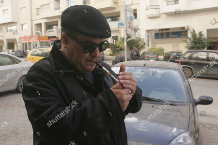 Stock Photo of Tunisian Dissident Journalist Taoufik Ben Brik Lights a Cigarette in Tunis Tunisia 21 January 2011 According to Local Media Reports Ben Brik Has Announced He Would Be Candidate For the Next Presidential Elections in Tunisia Tunisians Began a Three-day National Mourning Period on 21 January in Memory of the Victims of the Latest Events Which Led to the Departure of Former President Zine El-abedine Ben Ali and the Formation of an Interim Government Tunisia Tunis