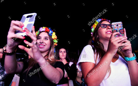 """Fans of Uruguayan singer and actress Natalia Oreiro photograph her tribute concert to the late Argentine cumbia singer Gilda, in Montevideo, Uruguay, late . Oreiro starred in the recent film biopic """"No me arrepiento de este amor"""" about Gilda's life and career"""