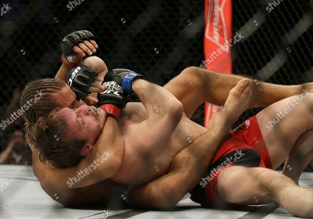 Urijah Faber, left, grapples Brad Pickett during a UFC Fight Night mixed martial arts fight in Sacramento, Calif