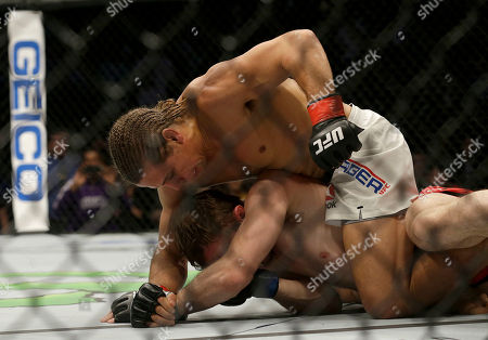 Urijah Faber, top, punches Brad Pickett during a UFC Fight Night mixed martial arts fight in Sacramento, Calif