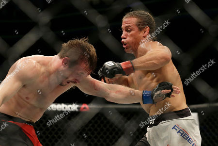 Urijah Faber, right, punches Brad Pickett during a UFC Fight Night mixed martial arts fight in Sacramento, Calif