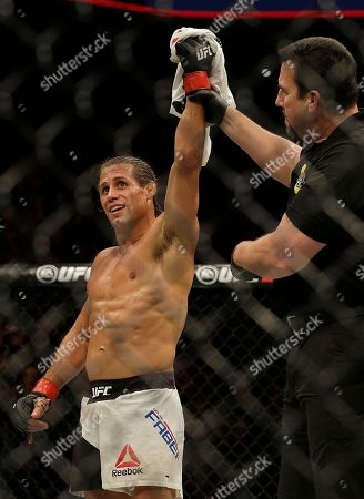 Urijah Faber has his arm raised after beating Brad Pickett during a UFC Fight Night mixed martial arts fight in Sacramento, Calif