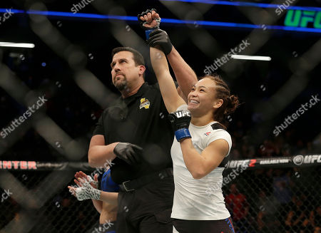 Michelle Waterson has her arm raised after beating Paige VanZant in a UFC Fight Night mixed martial arts fight in Sacramento, Calif