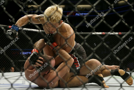 Mizuto Hirota, top, punches Cole Miller during a UFC Fight Night mixed martial arts fight in Sacramento, Calif