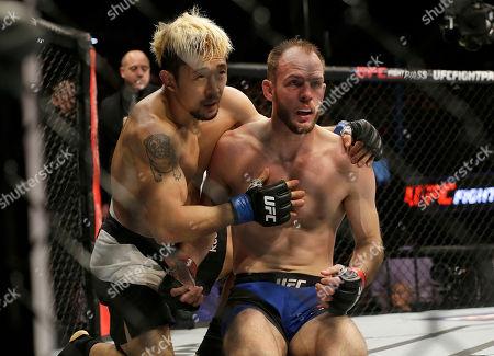 Mizuto Hirota, left, hugs Cole Miller after a UFC Fight Night mixed martial arts fight, won by Hirota, in Sacramento, Calif