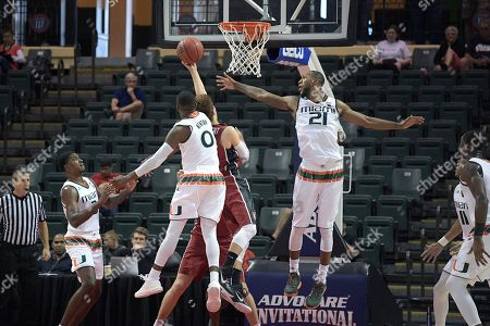 Stanford guard Robert Cartwright (2) goes up for a shot between Miami guard Ja'Quan Newton (0) and forward Kamari Murphy (21) during the second half of an NCAA college basketball game at the AdvoCare Invitational tournament in Lake Buena Vista, Fla., . Miami won 67-53