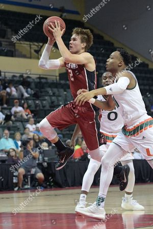 Stanford guard Robert Cartwright (2) goes up for a shot in front of Miami guard Ja'Quan Newton (0) and guard Bruce Brown (11) during the second half of an NCAA college basketball game at the AdvoCare Invitational tournament in Lake Buena Vista, Fla., . Miami won 67-53
