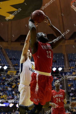 Randy Phillips, Nathan Adrian Radford center Randy Phillips (32) drives to the basket as West Virginia forward Nathan Adrian (11) attempts to block him from behind during the second half of an NCAA college basketball game, in Morgantown, W.Va