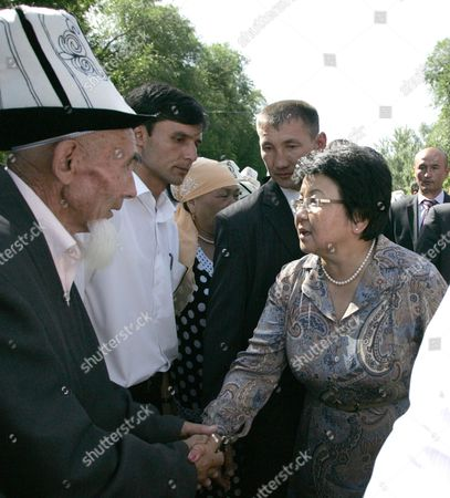 Kyrgyz President Roza Otunbayeva Shakes Hands with a Kyrgyz Elder As She Visits a Ceremony of Remembrance of Massacre Victims in the City of Osh 10 June 2011 Kyrgyz Officials and Representatives of Uzbek and Kyrgyz Communities Gathered to Commemorate the Hundreds of Victims Mostly Uzbeks Killed in the Massacre Which Happened in the Country's Ethnically Divided South a Year Ago Kyrgyzstan Osh