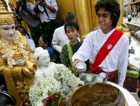 Myanmar Democracy Leader Aung San Suu Kyi (2-r) Looks on As Her Son Kim Aris (r) Offers Water to a Buddha Image at the Shwedagon Pagoda in Yangon Myanmar 12 July 2011 Suu Kyi Will Go on a Political Tour After Martyr's Day on 19 July 2011 Myanmar Yangon
