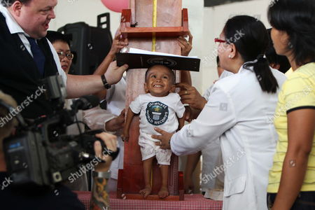 Craig Glenday of Guinness World Records (l) Measures the Height of Junrey Balawing (c) who is Celebrating His 18th Birthday During a Ceremony Inside a Municipal Hall in Sindangan Zamboanga Del Norte Southern Philipipines on 12 June 2011 Junrey who is 23 59 Inches Or 59 93 Centimeters Tall Struggles to Walk and Can't Stand Too Long Replaced Nepalese Khagendra Megar who Stands 26 4 Inches For Distinction 'We Are Very Proud of Him ' Said His Mother Concepcion Philippines Sindangan