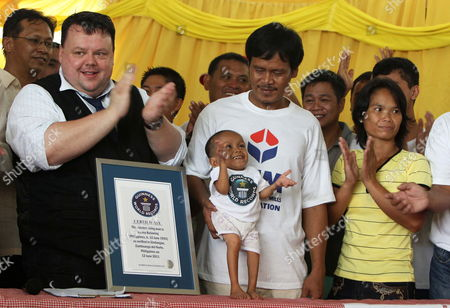 Craig Glenday of Guinness World Records (l) Celebrates with Junrey Balawing who is Celebrating His 18th Birthday (c) Standing Next to a Guinness World Records Ceritificate Crowned As the Shortest Living Man During a Ceremony Inside a Municipal Hall in Sindangan Zamboanga Del Norte Southern Philipipines on 12 June 2011 Junrey a 23 59 Inches Or 59 93 Centimeters Tall who Struggles to Walk and Can't Stand Too Long Replaced Nepalese Khagendra Megar who Stands 26 4 Inches For Distinction 'We Are Very Proud of Him ' Said His Mother Concepcion Philippines Sindangan