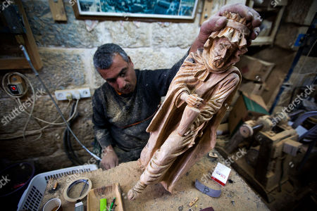 Palestinian woodcarver Muhammad Yusuf, works on olive wood figures in the West Bank city of Bethlehem. Christmas is approaching and pilgrims and tourists have begun to arrive, crowding the souvenir shops that line the narrow streets and allies of the city where Jesus is said to have been born. But when visitors choose to take a piece of the Holy Land back home with them, they better check the labels. Many souvenirs, including the West Bank town's trademark rosemary beads, are imported from abroad, mainly China