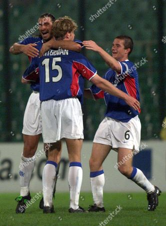 Warsaw Poland : Dutchman Bert Konterman (15) Celebrates with His Team-mates Italian Lorenzo Amoruso (l) and Barry Ferguson From Rangers Fc After Scoring a Goal During Uefa Cup Match with Anzhi Makhachkala in Warsaw on 27 September 2001