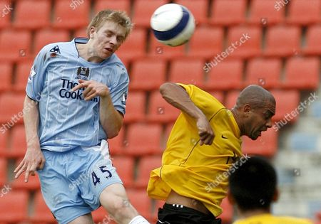 Manchester City's Benjamin Mee (l) in a Mid-air Heading Duel with Thailand Premier All Star's Brazilian Forward Ney Fabiano Oliviera (r)during Their Friendly Soccer Match at Rajamangala Stadium in Bangkok Thailand 17 May 2008