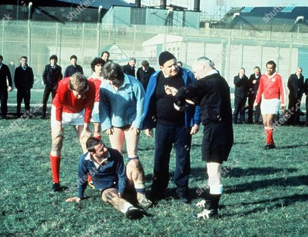 'Porridge'  Film - 1979 - Norman Stanley Fletcher (Ronnie Barker) talks with and Mr Mackay (Fulton Mackay), the referee, as football players stand about