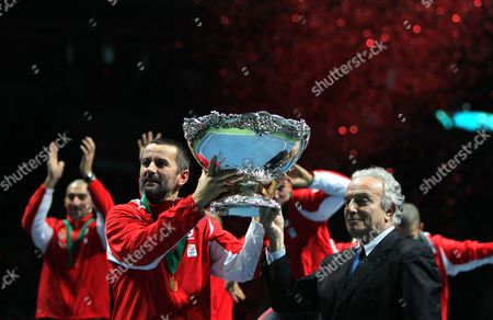 Serbia's Davis Cup Team Captain Bogdan Obradovic (l) Receives the Davis Cup Trophy From Itf President Francesco Ricci Bitti After the Tennis Davis Cup Final Match at the Belgrade Arena in Belgrade Serbia on 05 December 2010 First-time Finalist Serbia Completed an Impossible Dream 05 December As Novak Djokovic and Viktor Troicki Came Through Must-win Sunday Matches to Seal a 3-2 Victory Over France in the Davis Cup Final Immediately After the Initial Celebration on Court the Serb Players Lined Up Four Chairs and Began Shaving Their Heads in Line with a Promise They Made Serbia and Montenegro Belgrade