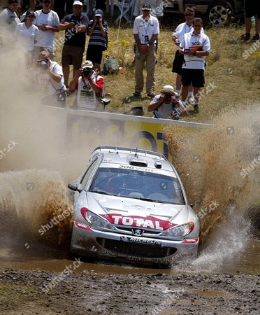 Elatia Greece : Great Britains Richard Burns and His Co-driver Robert Reid Blast Their Peugeot 206 Wrc Through the Muddy Waters of the Elatia Special Stage in Central Greece During the Second Leg of the 49th Rally Acropolis Saturday 15 June 2002 Burns is Second While Mcrae Leads the Race After the 9th Special Stage of the Second Day of the Rally