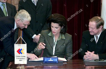 Budapest Hungary : Us Ambassador to Hungary Nancy Goodman Brinker (c) Prepares to Sign the Cyber Crime Convention Declaration in Budapest on Friday 23 November 2001 As Council of Europes Director General of Legal Affairs Guy De Vel (l) and Deputy Secretary-general of the European Council Hans Christian Krueger (r) Look on