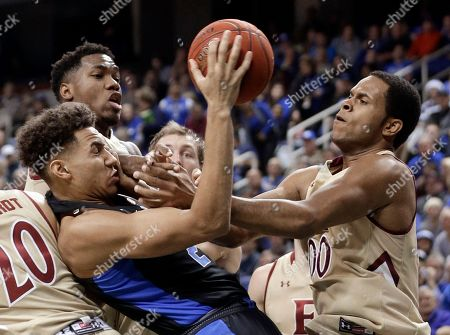 Duke's Chase Jeter, left, and Elon's Steven Santa Ana, right, battle for a rebound in the first half of an NCAA college basketball game in Greensboro, N.C
