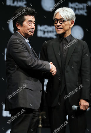 Stock Photo of Japanese composer Ryuichi Sakamoto, a member of the Yellow Magic Orchestra (YMO) is celebrated from his friend and a Japanese author Ryu Murakami (L) after he received Montblanc de la Culture Arts Patronage Award