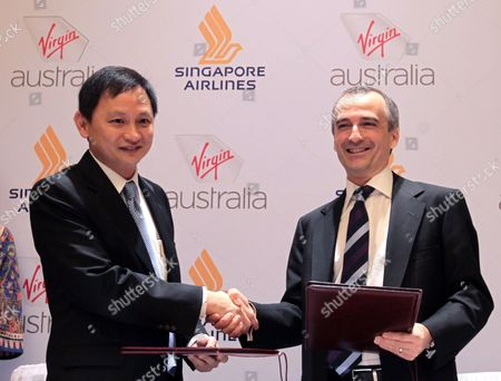 John Borghetti Ceo of Virgin Australia (r) and Goh Choon Phong Ceo of Singapore Airlines Exchange an Agreement During a Press Conference in Singapore on 07 June 2011 Singapore Airlines and Virgin Australia Have Signed a Long-term Partnership Deal Which Will Allow the Two Airlines to Codeshare on Each Other's International and Domestic Flights Singapore Singapore