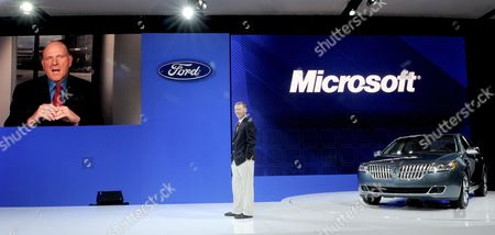 Stock Photo of Ford Motor Company President and Ceo Alan Mulally (c) Listens As Steven Ballmer (l) Ceo of Microsoft Corporation on a Video Screen Discusses a New Partnership Between the Two Companies a During a Press Conference at the New York International Auto Show at Jacob Javits Center in New York Usa 31 March 2010 United States New York