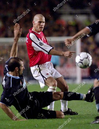 London United Kingdom : Arsenals Frederik Ljunberg (c) Threads a Pass Past a Sliding Giuseppe Pancaro (l) of Lazio During the Uefa Champions League Match at Highbury in London 27 September 2000 Ljunberg Scored Both Goals to Give Arsenal a 2-0 Victory