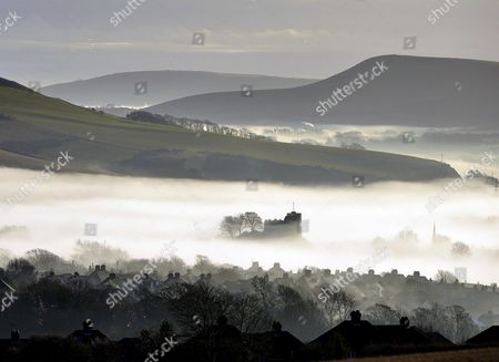 Lewes castle emerging from mist  with the South Downs national park surrounding, East Sussex on a calm day before Storm Barbara hits the UK