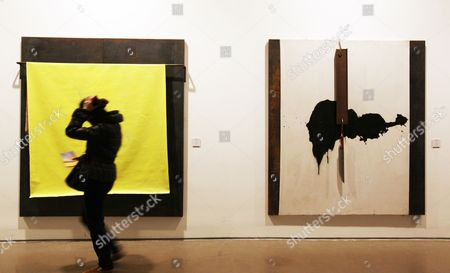 A Visitor Looks at Art Works by Greek Artist Jannis Kounellis As Part of an Exhibition Titled 'Translating China' in Today Art Museum in Beijing China 25 November 2011 a Master of the Arte Povera Movement Kounellis Uses Everyday Materials Like Porcelain Pieces Coal Steel Plates Copper Plates Clothes and Utensils to Create Works That Express His Thoughts on Chinese Society and Culture in His First Solo Exhibition in the Country the Exhibition Runs Till 13 December China Beijing