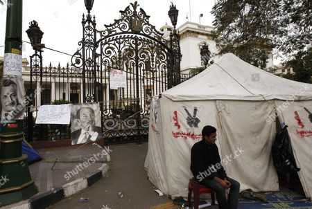 An Egyptian Protester Sits Next to the Six April Movement Tent As He Takes Part in the Continuing Sit-in at the Parliament and Prime Minister Office Street One Day Before the Run-off in the First Round of the Parliamentary Elections at the Parliament Gate in Cairo Egypt 04 December 2011 Behind Them is the Symbol of According to Media Reports the Decision on the New Egyptian Cabinet was Delayed Again on 03 December After Prime Minister-designate Kamal Al-ganzouri Said He Would Reconsider Some of the Nominations Many Activists Have Rejected Al-ganzouri Because of His Ties to the Mubarak Regime He Served As Prime Minister From 1996-1999 the Interim Ruling Supreme Council of the Armed Forces Appointed Al-ganzouri to Replace Outgoing Premier Essam Sharaf who Resigned After After 42 People Were Killed in Countrywide Clashes Between Protesters and Police in November the Clashes Were the Worst Since the January 25 Revolution Which Led to the Fall of Mubarak Egypt Has Seen Renewed Protests with Activists Pushing For the Military to Speed Up the Transfer of Power to a Civilian Government Egypt Cairo
