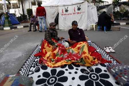 Egyptian Protesters Potect Themselves From Cold with Blankets As They Take Part in the Continuing Sit-in at the Parliament and Prime Minister Office Street One Day Before the Run-off in the First Round of the Parliamentary Elections Cairo Egypt 04 December 2011 Behind Them is the Symbol of the Six April Movement on a Tent According to Media Reports the Decision on the New Egyptian Cabinet was Delayed Again on 03 December After Prime Minister-designate Kamal Al-ganzouri Said He Would Reconsider Some of the Nominations Many Activists Have Rejected Al-ganzouri Because of His Ties to the Mubarak Regime He Served As Prime Minister From 1996-1999 the Interim Ruling Supreme Council of the Armed Forces Appointed Al-ganzouri to Replace Outgoing Premier Essam Sharaf who Resigned After After 42 People Were Killed in Countrywide Clashes Between Protesters and Police in November the Clashes Were the Worst Since the January 25 Revolution Which Led to the Fall of Mubarak Egypt Has Seen Renewed Protests with Activists Pushing For the Military to Speed Up the Transfer of Power to a Civilian Government Egypt Cairo
